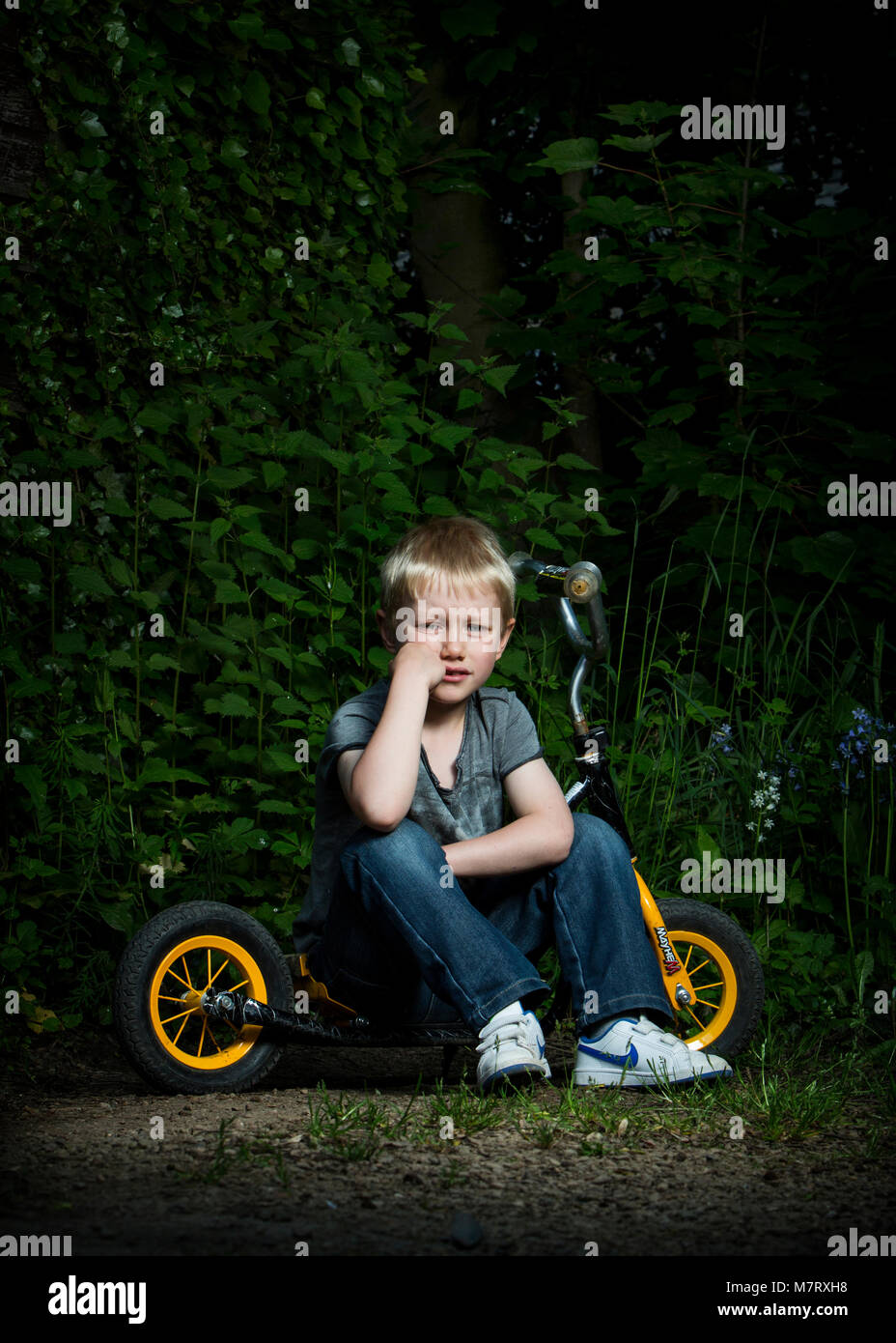 8 year old boy sat on a scooter on a rural path - Stock Image
