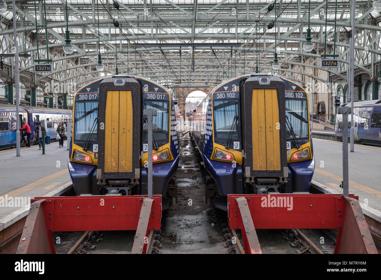 2 Siemens Class 380 Electric Trains side by side at Platforms 12 and 13 of Glasgow Central Train Station - Stock Image