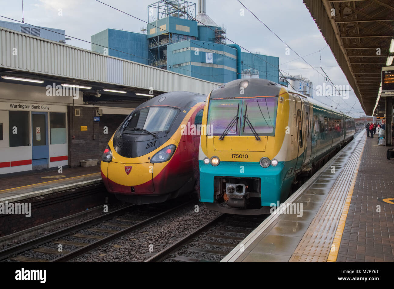 Two different generation Alstom manufactured trains at Warrington Bank Quay. On the left is a Class 390 Pendolino Stock Photo