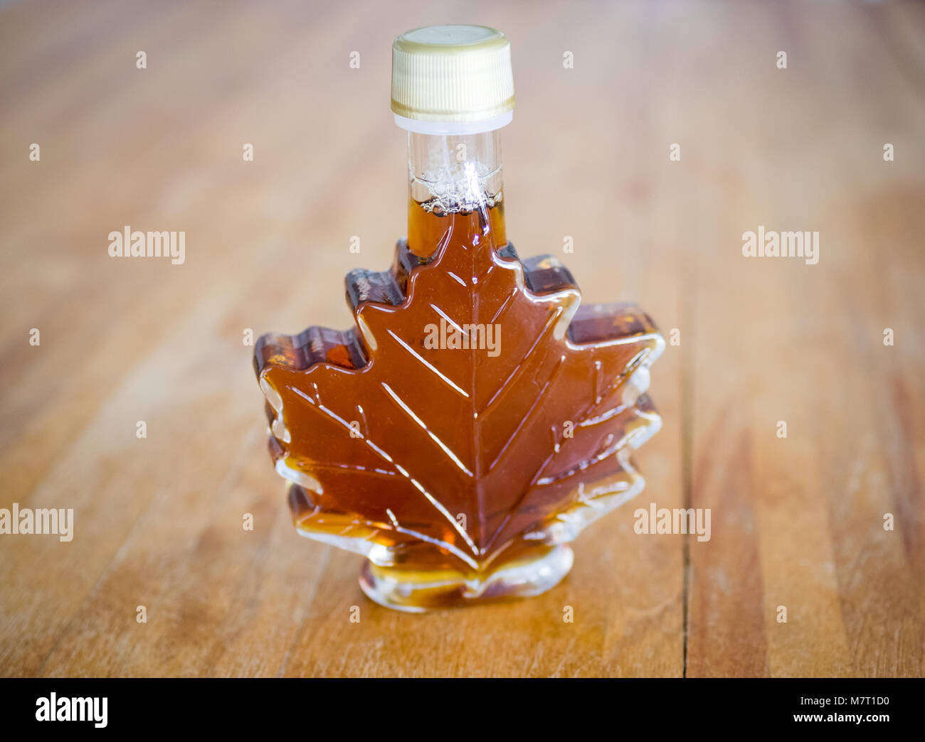 Real Canadian maple syrup in a glass maple syrup bottle. - Stock Image