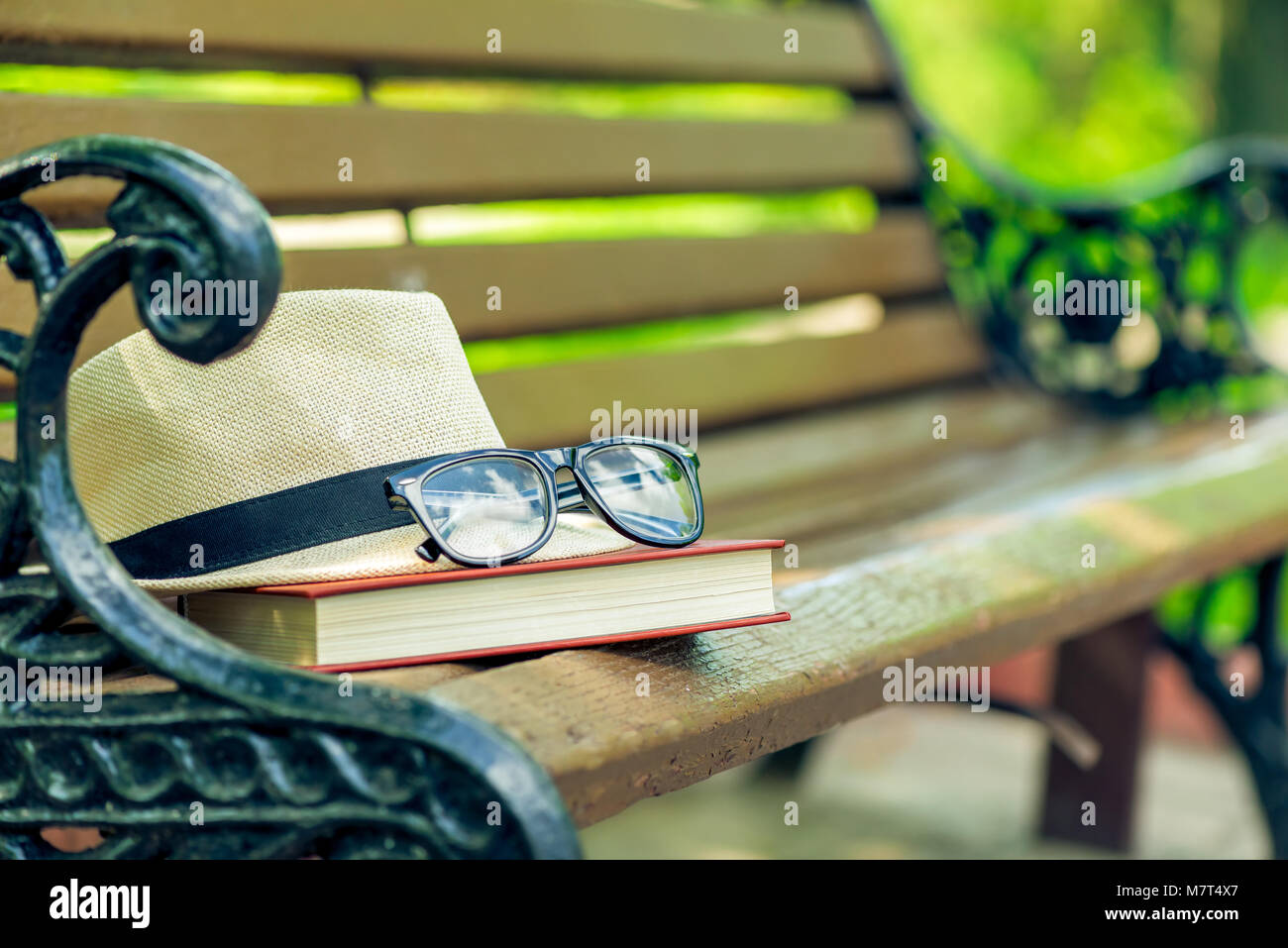 a forgotten book, a hat and glasses lie on the edge of a bench in a summer park - Stock Image