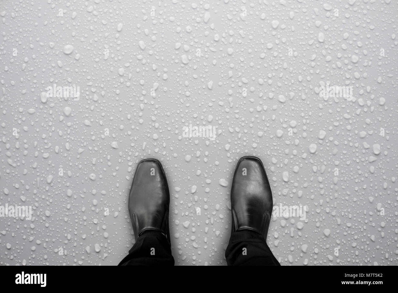 Businessman in black shoes standing on white wet floor. Water drop on the floor. Caution, slippery floor. - Stock Image