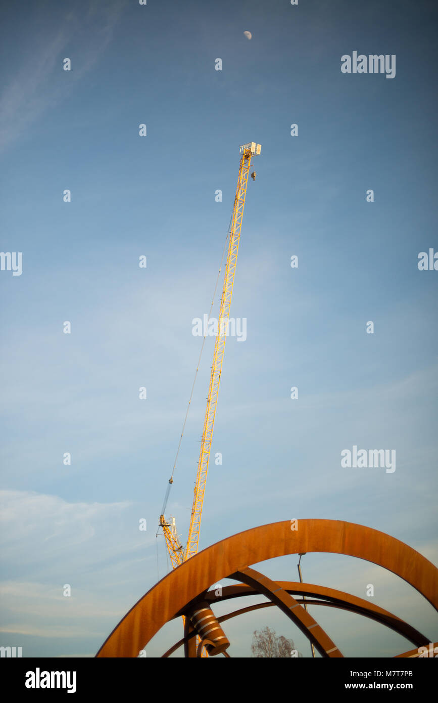 bright orange rusty sculpture with yellow tower crane and daylight moon in the background Stock Photo