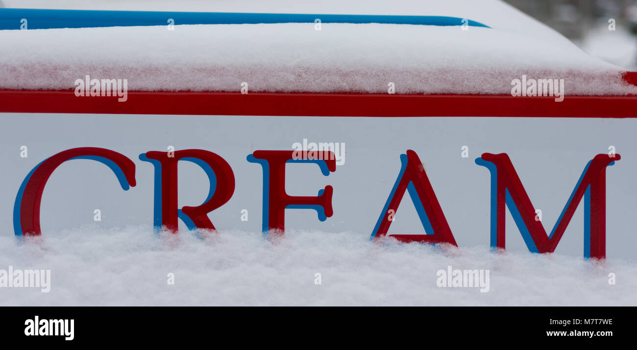 Red and white sign saying cream with ice and snow in background Stock Photo