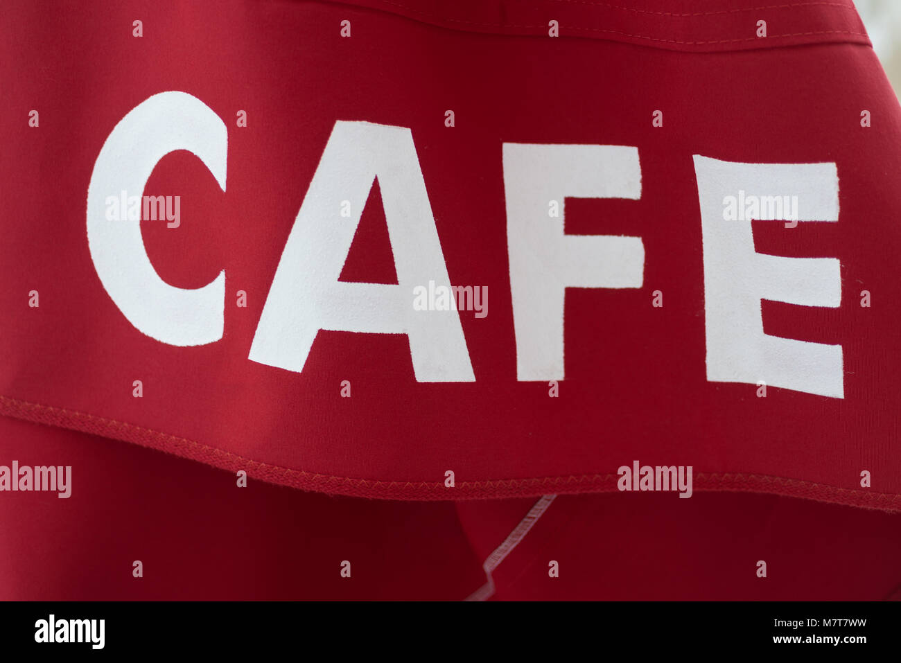 bright red and white cafe sign banner on cloth material - Stock Image