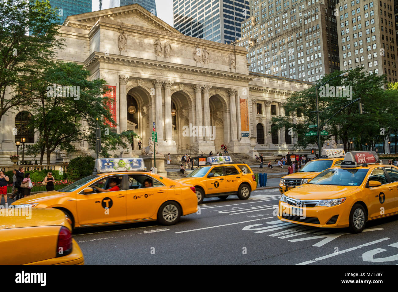Yellow New York taxis driving past The New York Public Library on 5th Avenue , Manhattan ,New York City - Stock Image