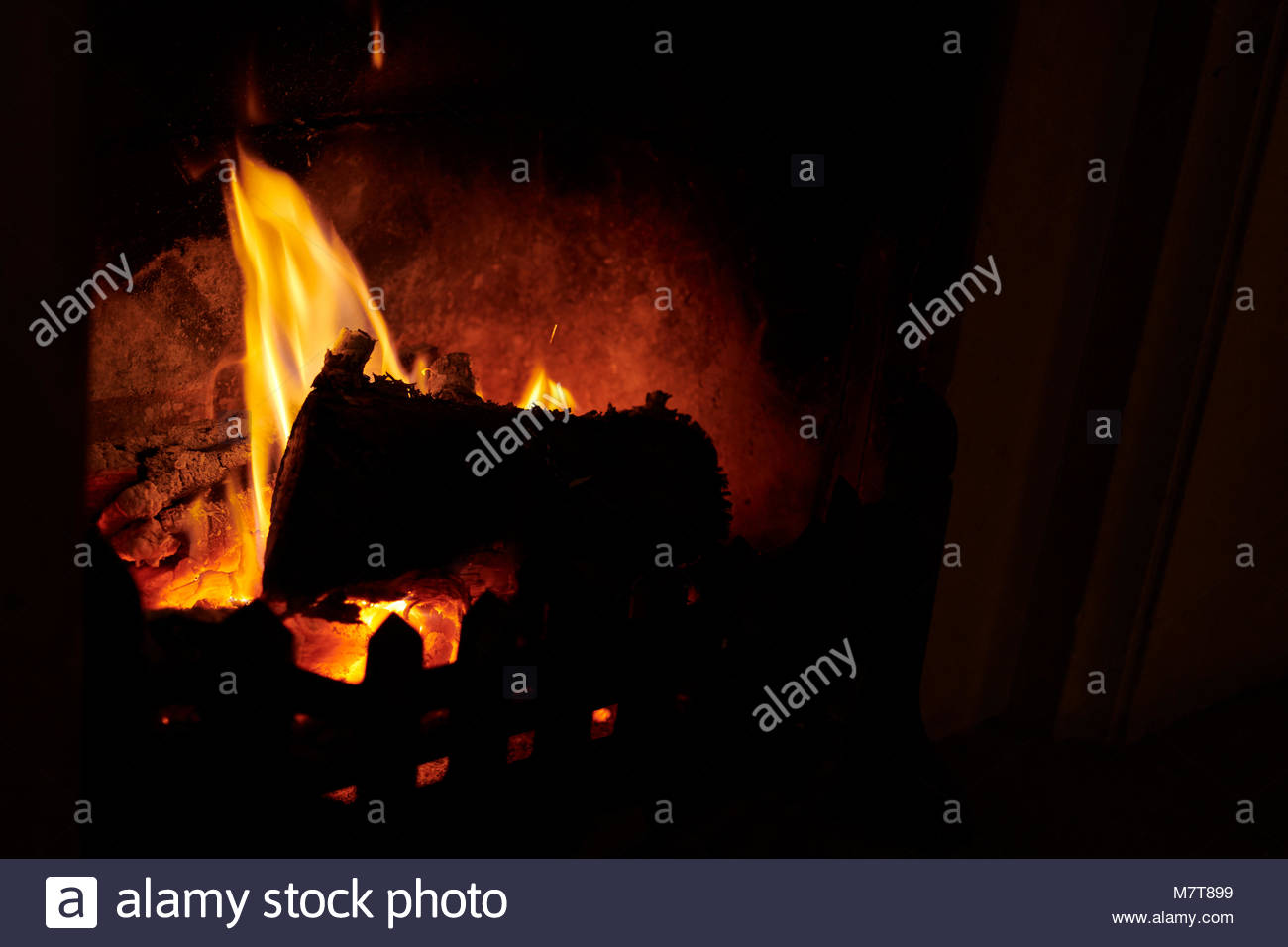 Flaming log in fire keeping the room warm in winter - Stock Image
