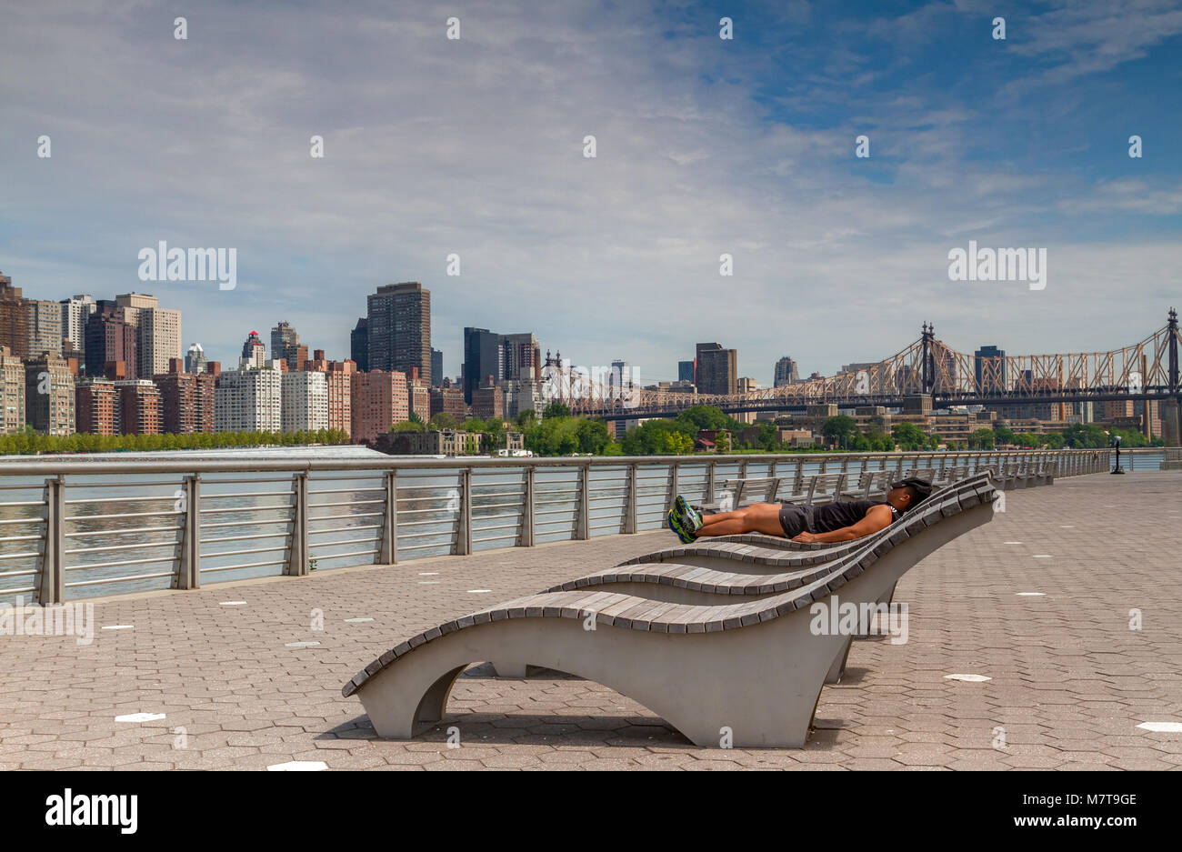 Man sunbathing on a wooden sun lounger in Gantry Plaza State Park across the East River from Manhattan with the Queensboro Bridge in the distance Stock Photo