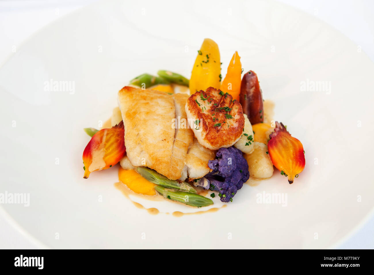 Fillet of fish with a scallop and served with vegetables - Stock Image