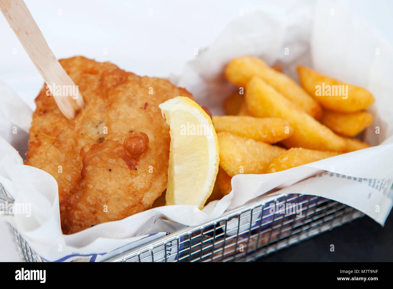 Fish and chips, with a chip fork in a metal basket. - Stock Image