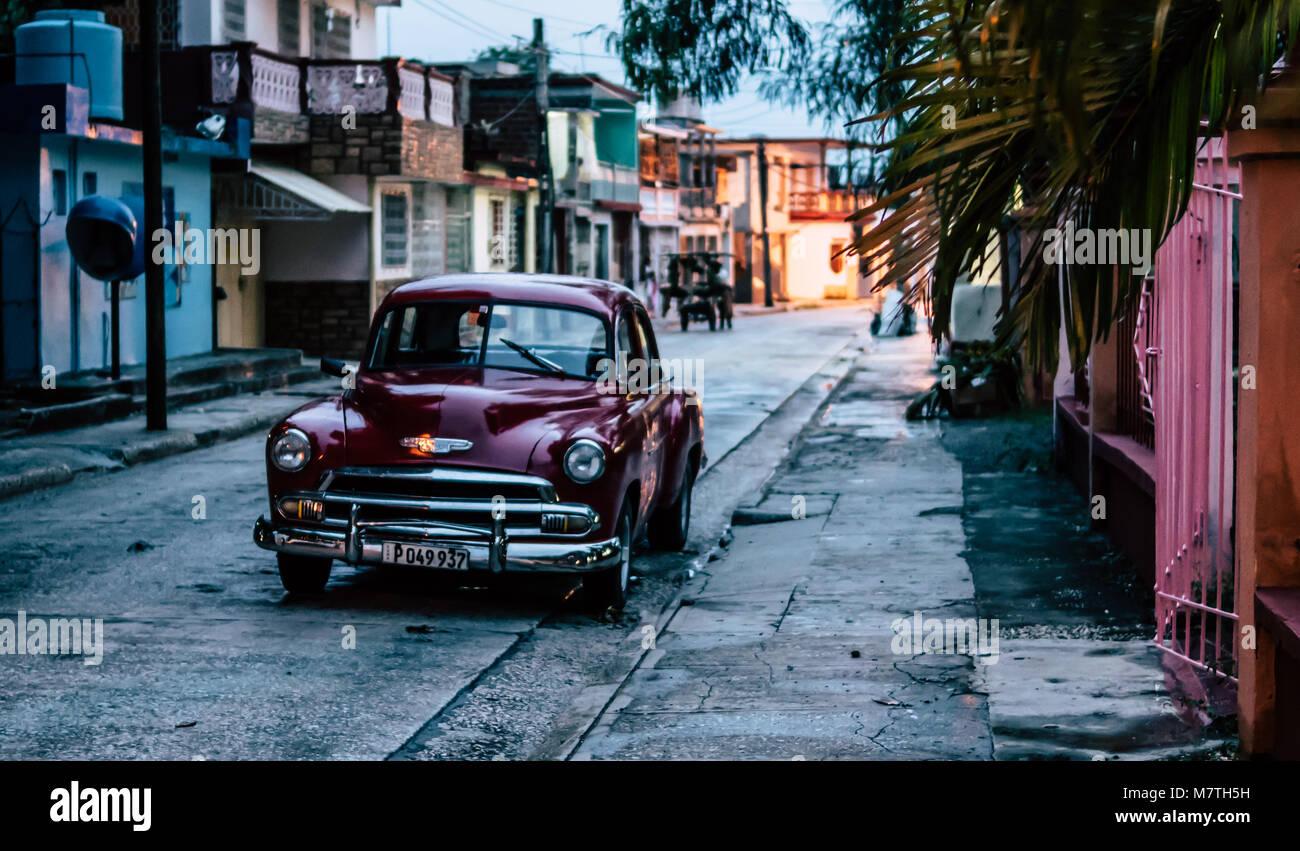 Holguin, Cuba - August 31, 2017: A shiny american classic car parked on a street at dusk. Stock Photo