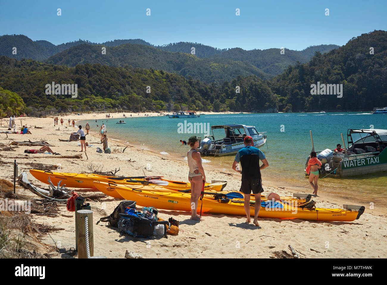 Kayaks and water taxis at Anchorage Beach, Abel Tasman National Park, Nelson Region, South Island, New Zealand - Stock Image