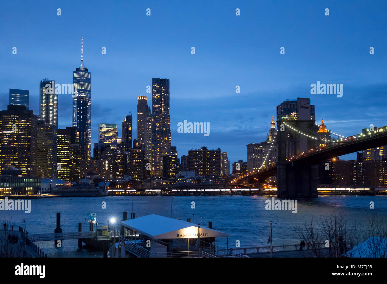 The Lower Manhattan skyline and the Brooklyn Bridge as seen across the East River from Dumbo Brooklyn at night - Stock Image