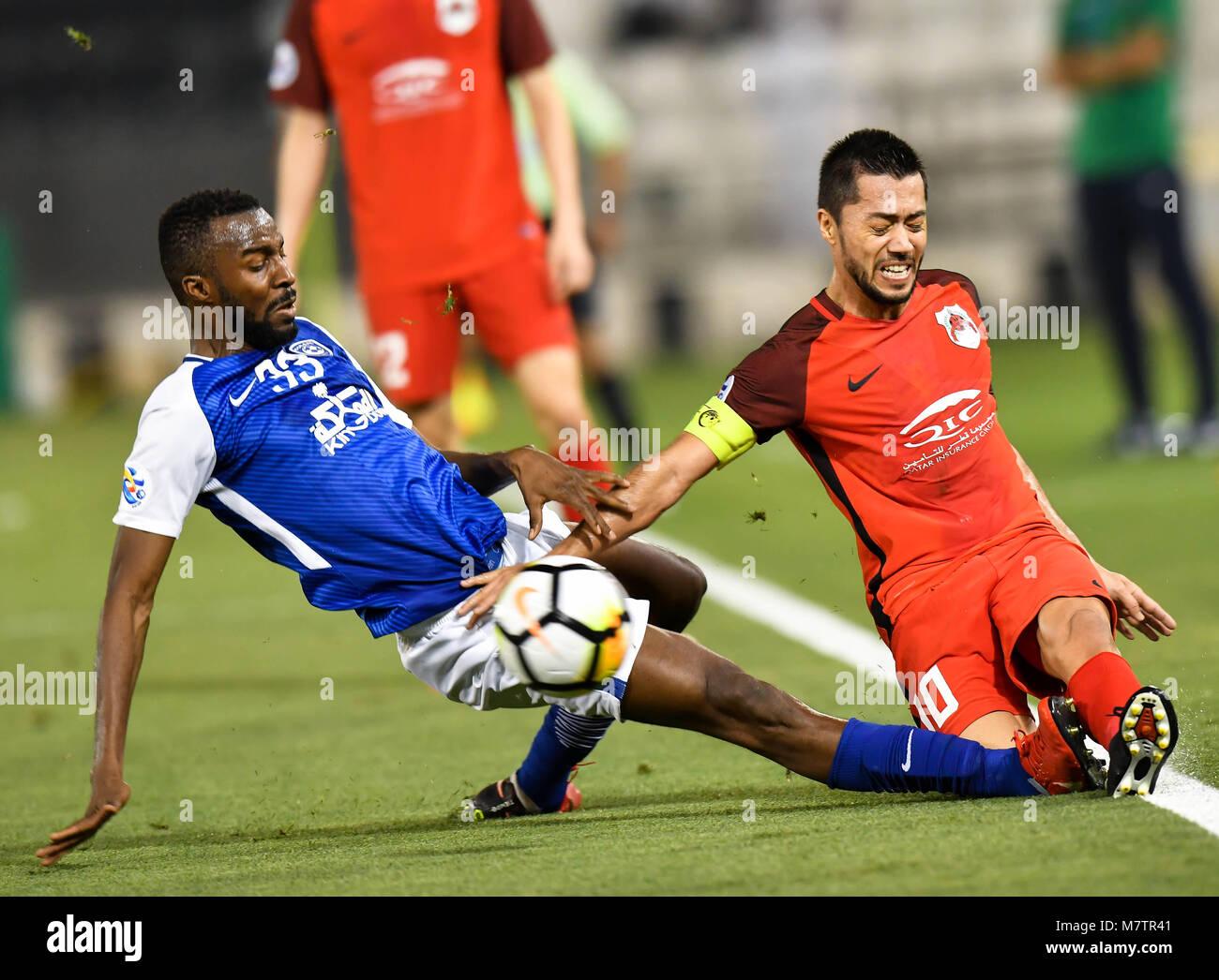 (180313) -- DOHA, March 13, 2018 (Xinhua) -- Osama Hawsawi (L) of Al-Hilal FC vies with Rodrigo Tabata of Al-Rayyan Stock Photo