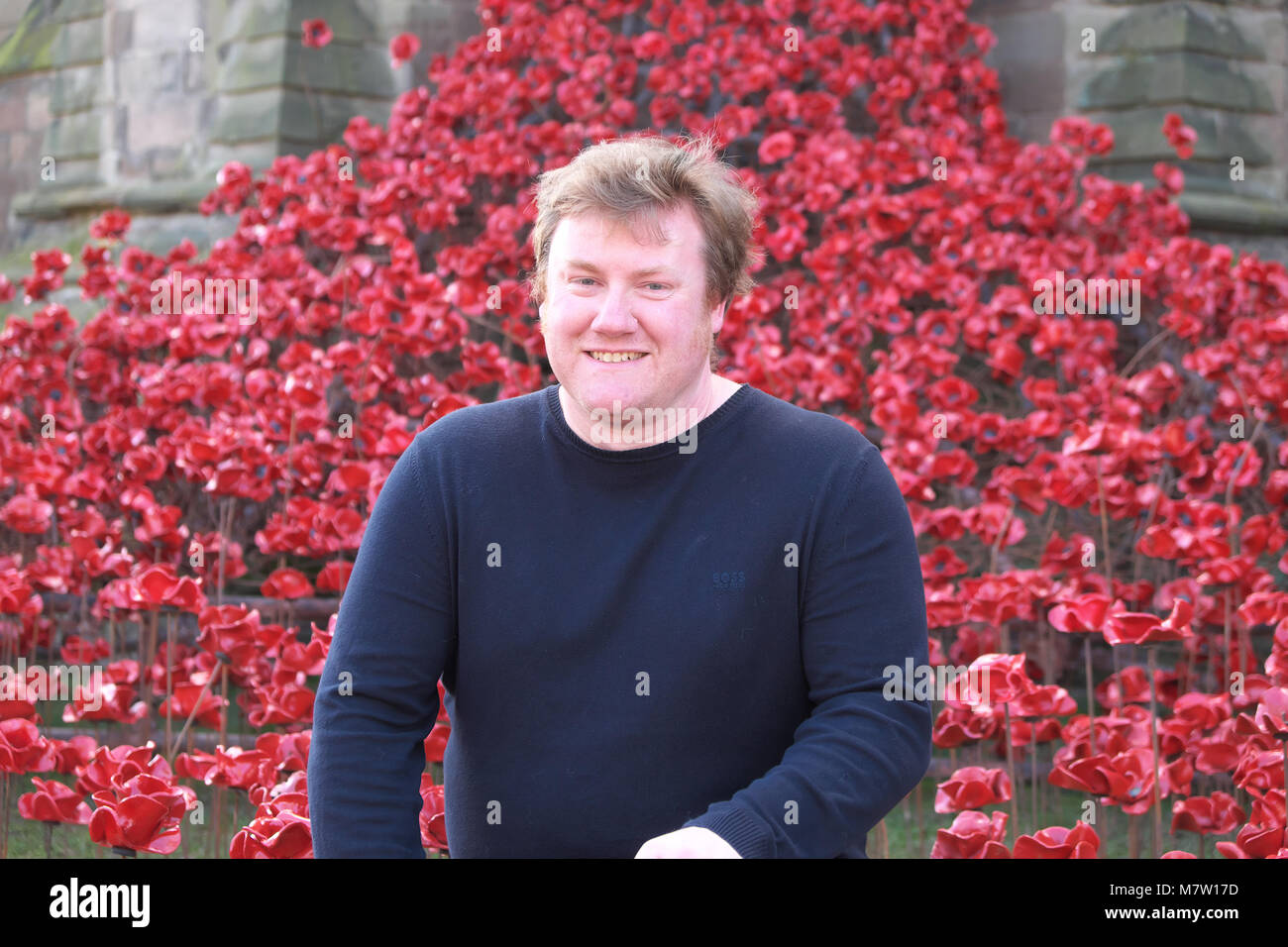 Hereford Cathedral, Hereford - Tuesday 13th March 2018 - Artist Paul Cummins in front of his poppy sculpture Weeping - Stock Image