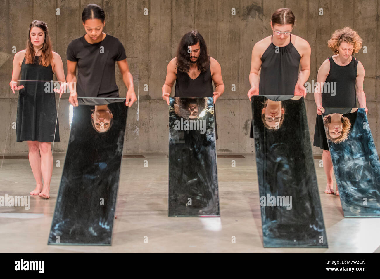 London, UK. 13th March, 2018. Mirror Piece II, an early work in which a group of performers make choreographed movements Stock Photo