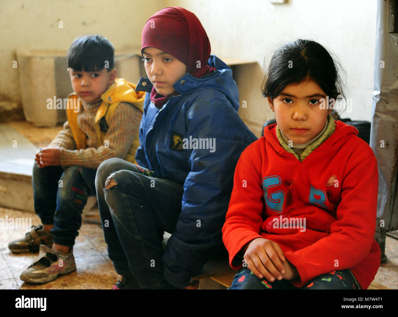 (180313) -- DAMASCUS, March 13, 2018 (Xinhua) -- Evacuated children sit in a temporary shelter in Wafidin area, Stock Photo