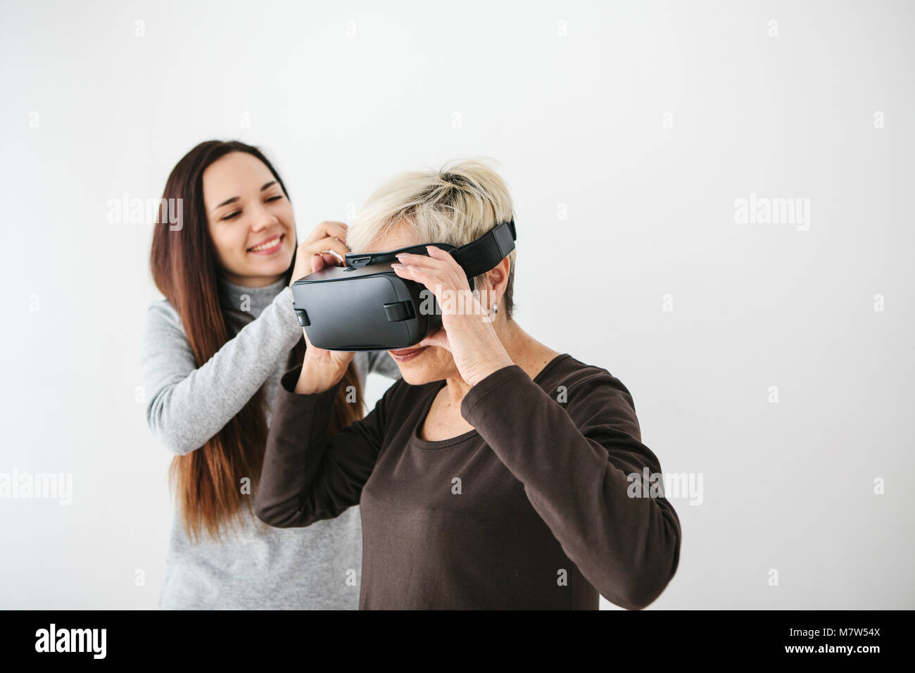A young girl explains to an elderly woman how to use virtual reality glasses. The older generation and new technologies. - Stock Image