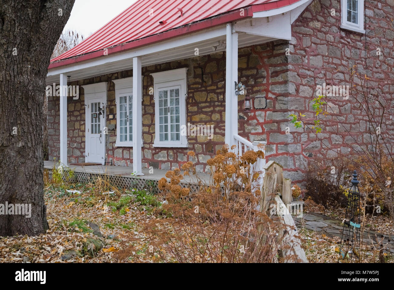 Superior Old Canadiana Circa 1831 Cottage Style Residential Home With Quarry Stone  Exterior In Autumn.