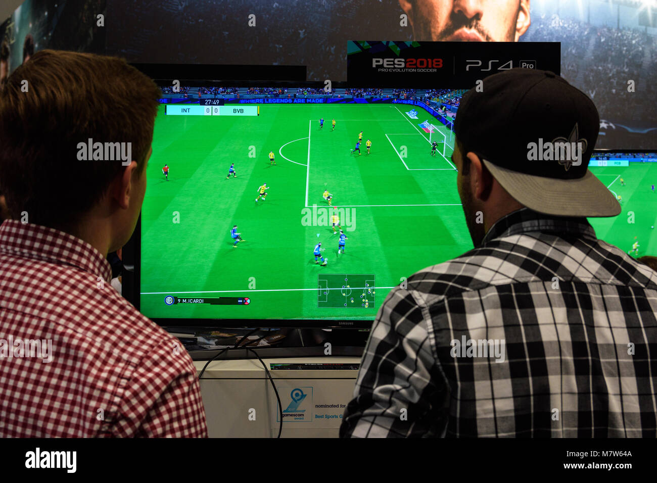 Cologne, Germany - August 24, 2017: Two fair visitors play the game Pro Evolution Soccer at the booth of the company - Stock Image