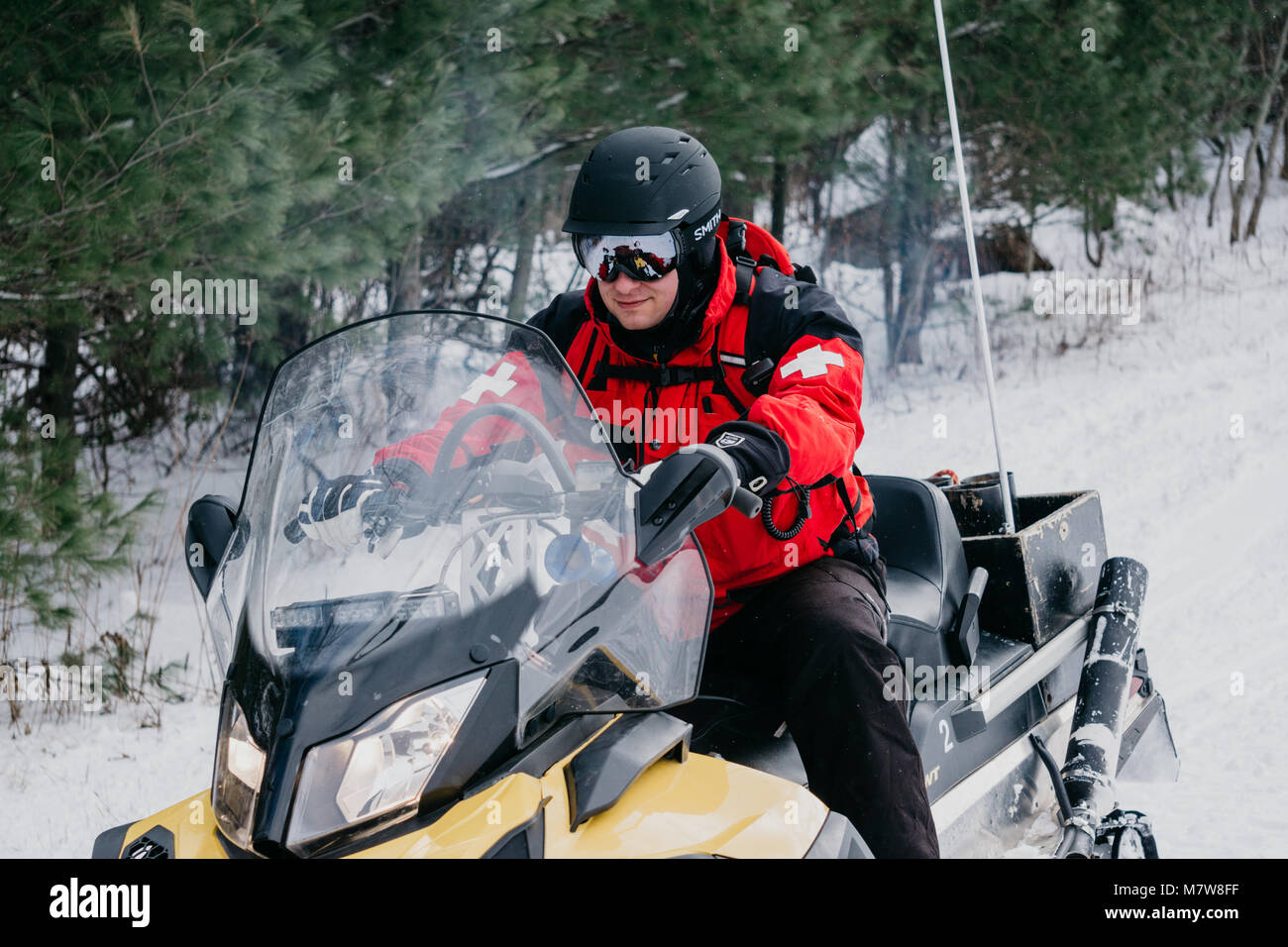Ski patroller riding snowmobile - Stock Image