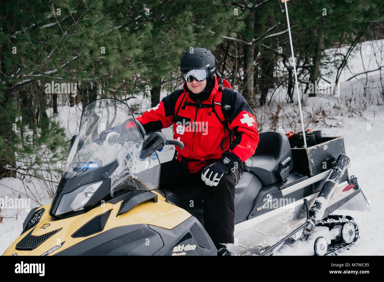 Ski Patroller on snowmobile - Stock Image