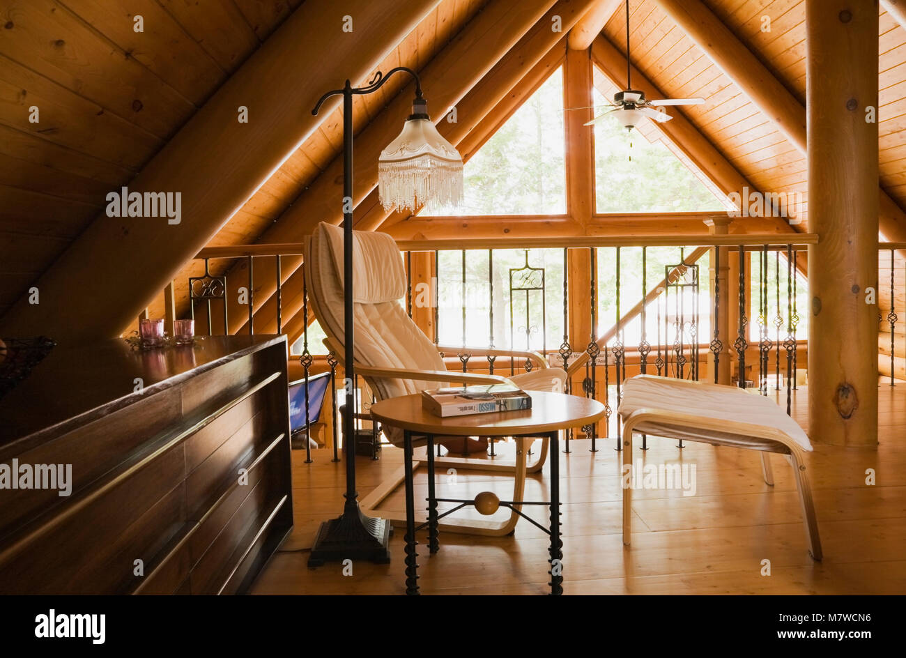 Wood and white leather armchair in the master bedroom on the upstairs floor inside a residential log home. - Stock Image