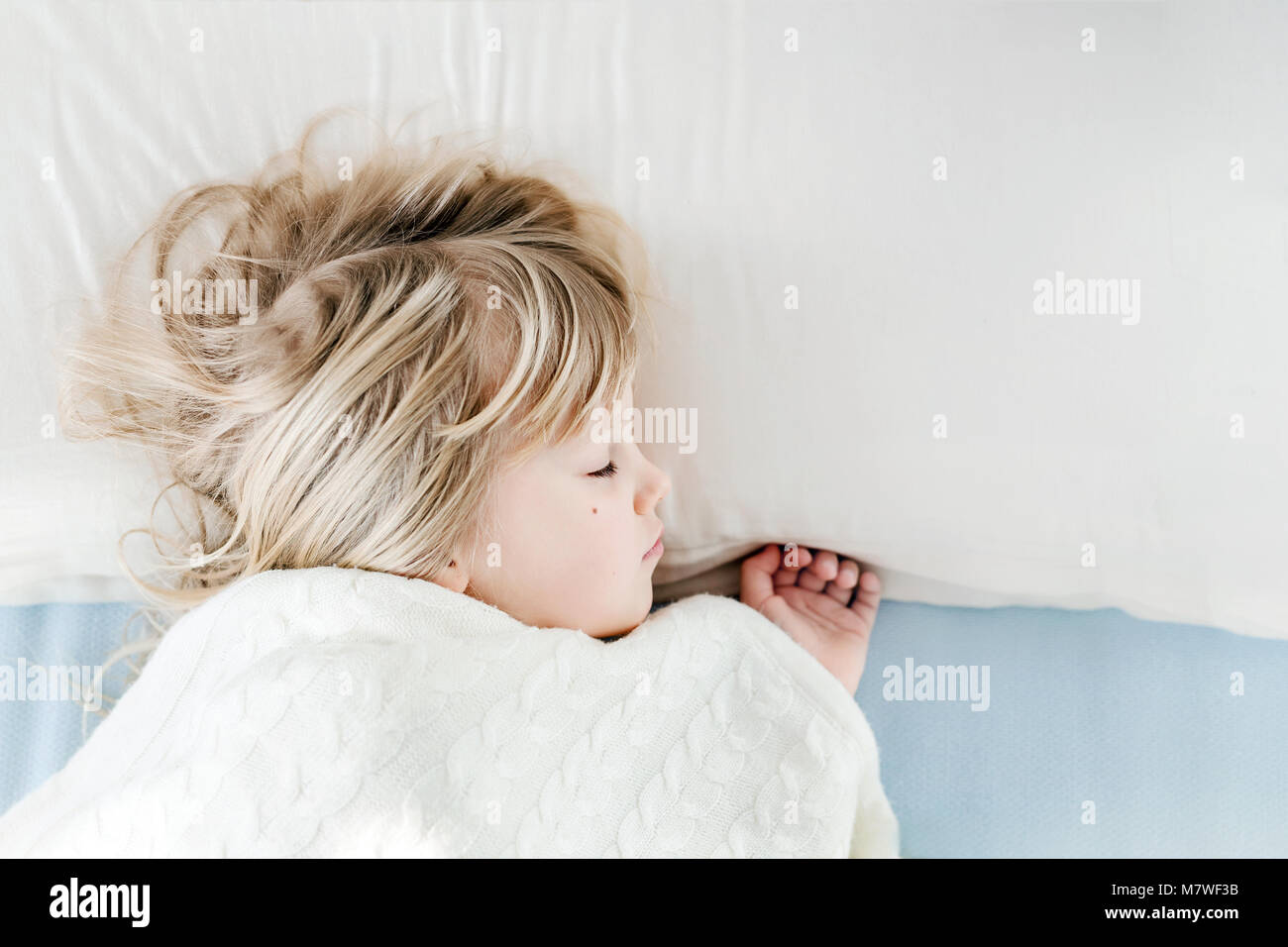 Little cute girl sleeping on pillow in bed  Kid covered with warm