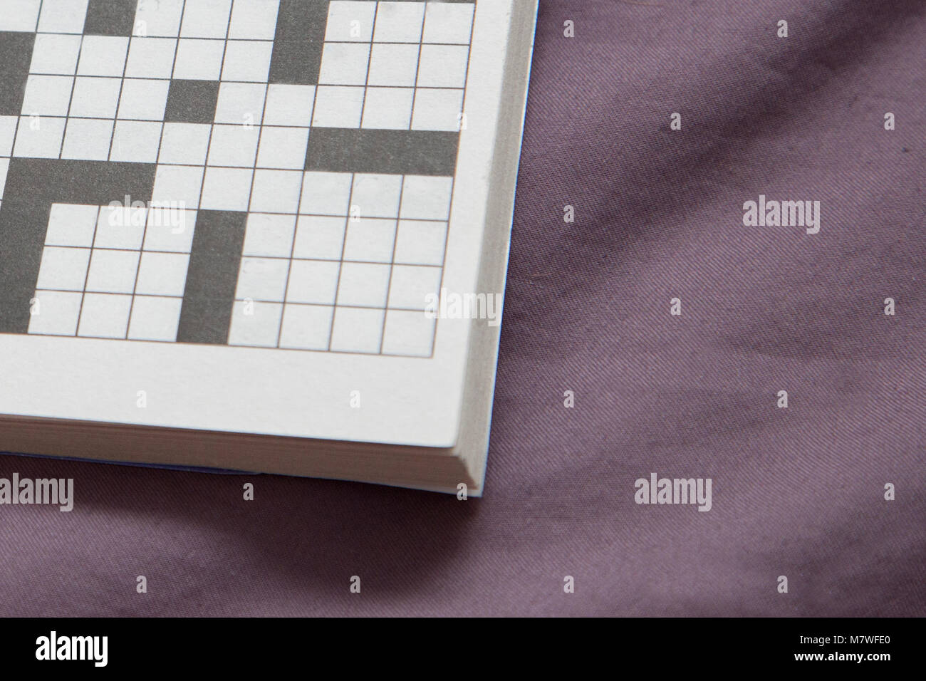 a crossword puzzle with empty spaces on a purple copy space - Stock Image