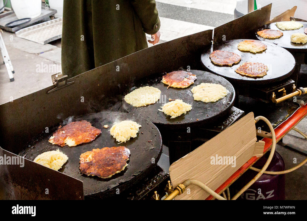 Les Gustalins stall and galettes d'oignon pomme de terre fromage (onion potato cheese pancakes) cooking on the - Stock Image