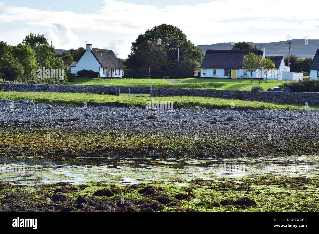 White country cottages with thatched roof in village of Ballyvaughan on west coast of Ireland. - Stock Image