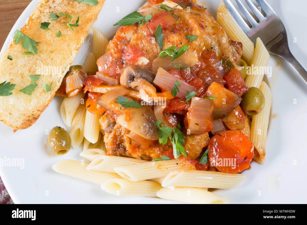 A portion of Italian style Chicken Cacciatore served with penne pasta and Garlic bread. - Stock Image