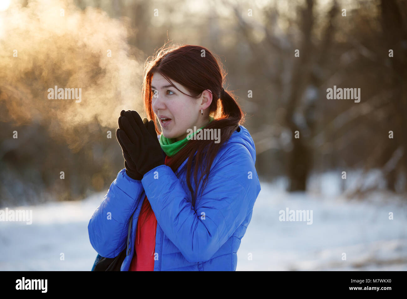 Picture of sporty woman warming her hands in winter forest - Stock Image