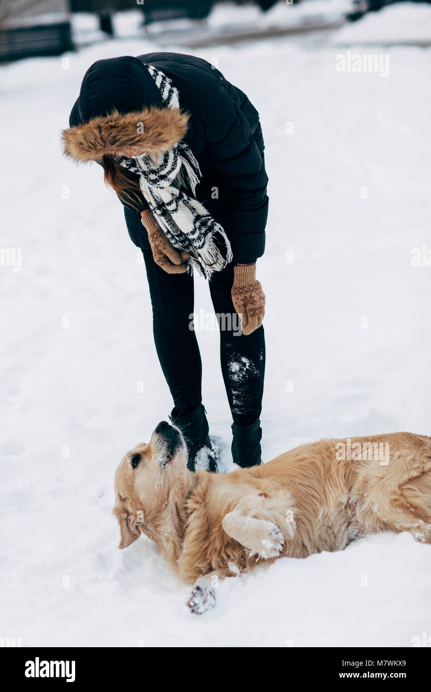 Image of girl in black jacket with retriever on walk in winter park - Stock Image