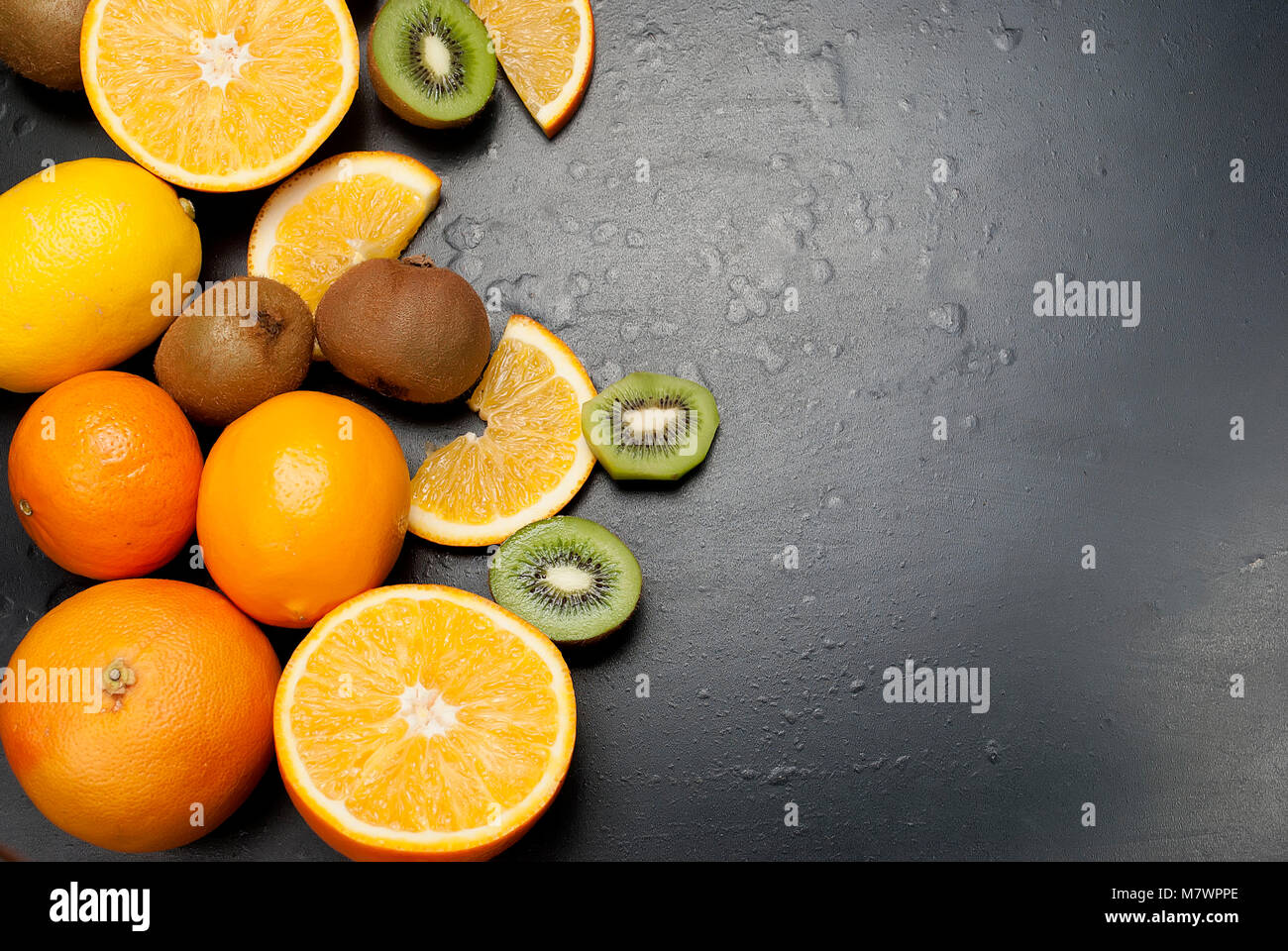 Variety of fresh citrus fruits on dark background from slices of kiwi and orange ,copy space - Stock Image