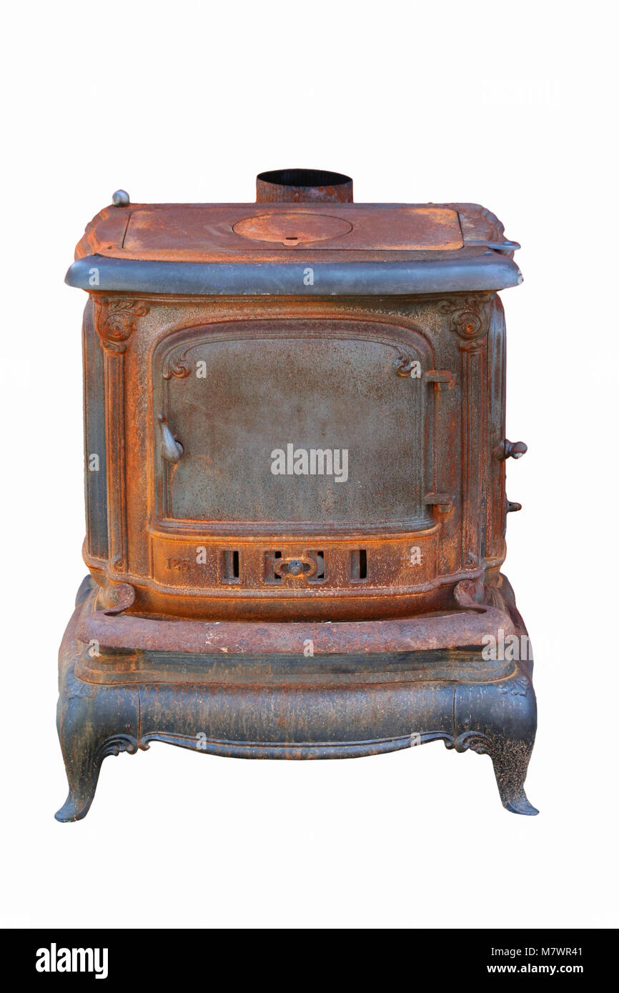 A Old rusty cast iron stove next to a barn - Stock Image