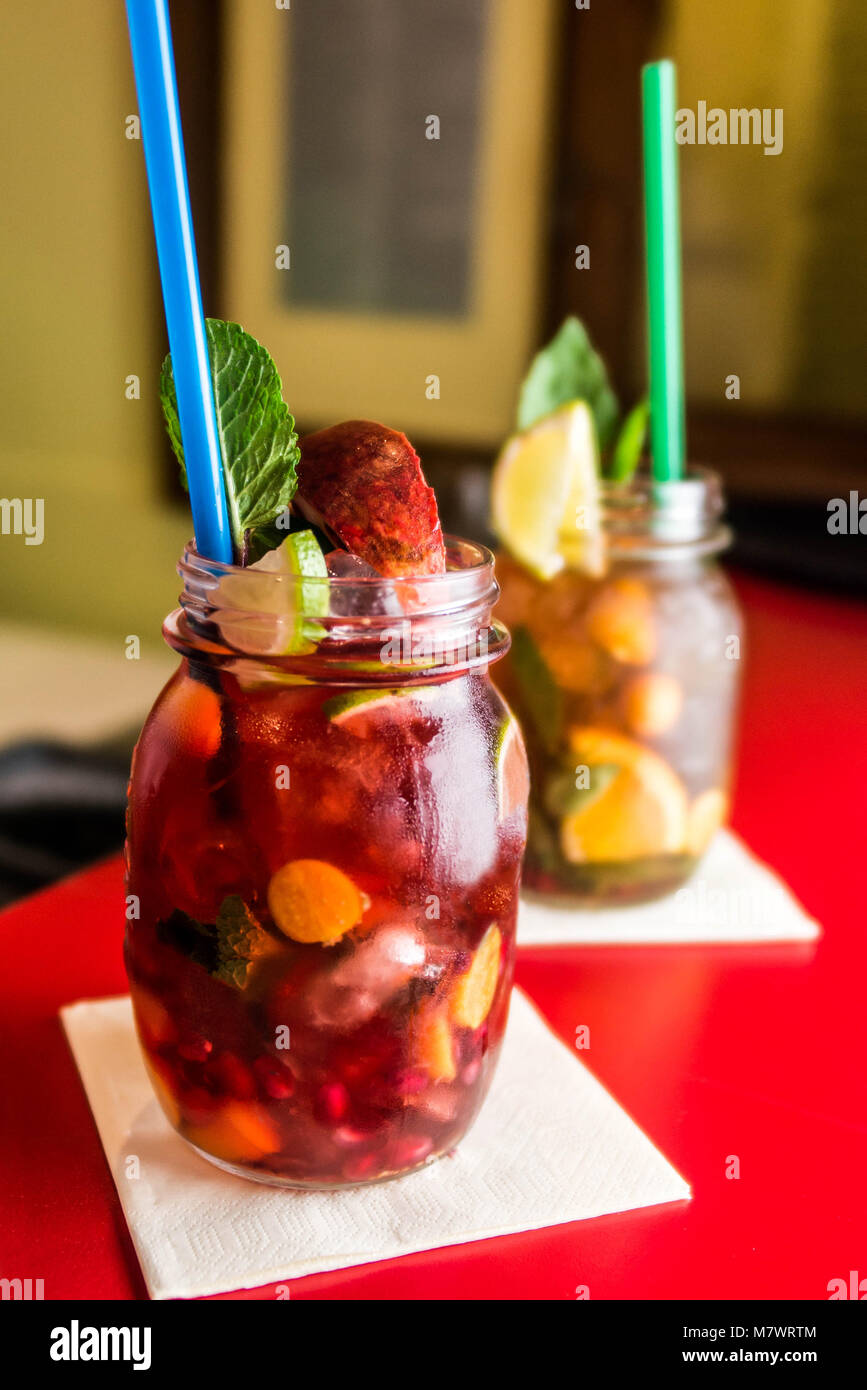 Homemade lemonade ice tea colorful icetea drink with fresh sweet fruits mint leaves in glass on the rocks with a - Stock Image