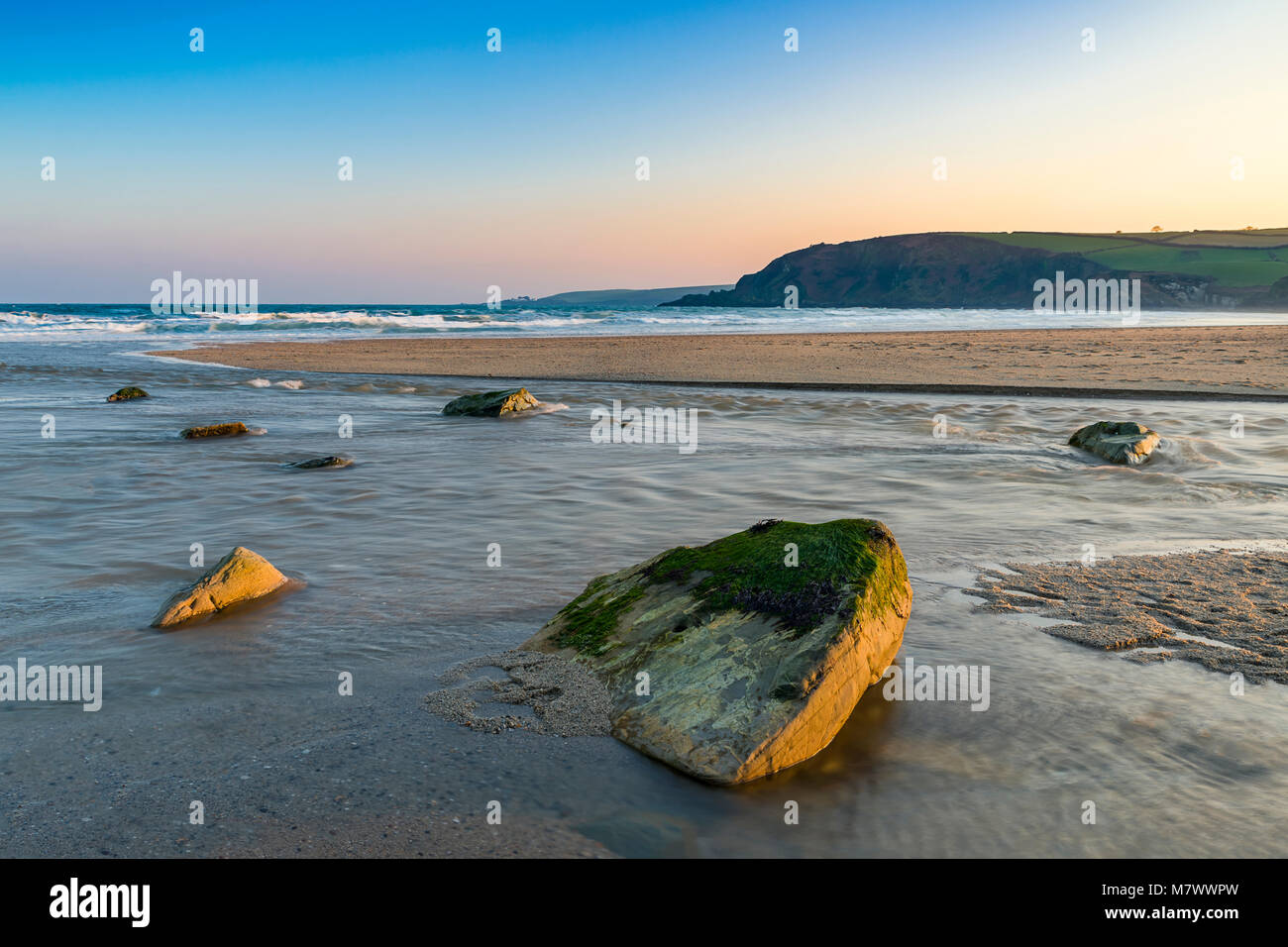 Sun Blushed Rocks Rest Against a Rivers Final Journey at Pentawen Sands in Cornwall - Stock Image