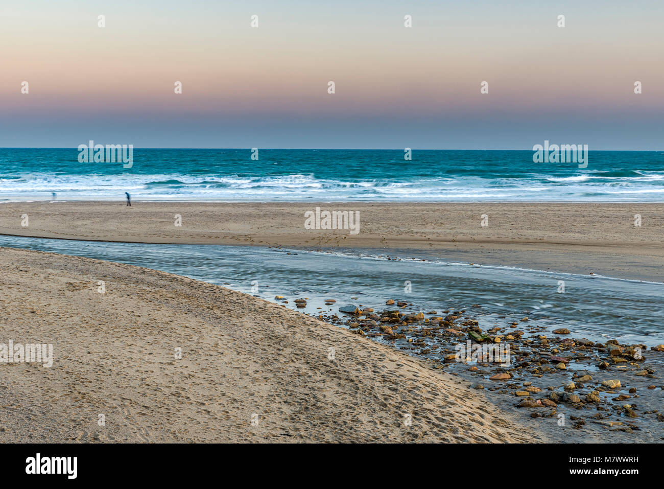 A Bend in a Small Beach Estuary at Sundown on Pentawen Sands, the people are too blurred to make out any defining - Stock Image