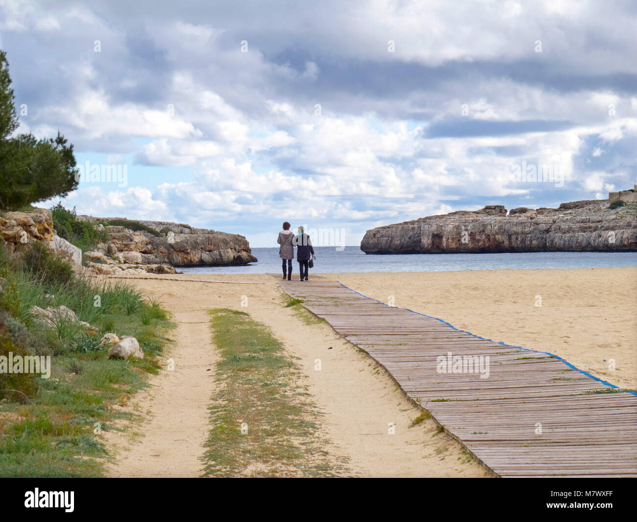Two elderly people standing on board walk looking out to sea - Stock Image