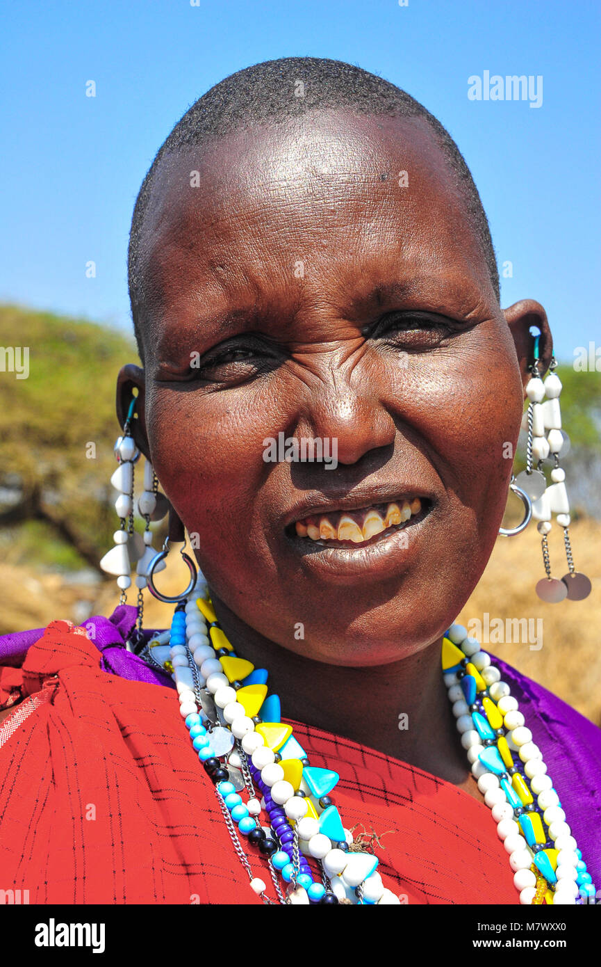 Close up portrait of a Masaai woman wearing traditional red robes and colourful necklace and earrings - Stock Image