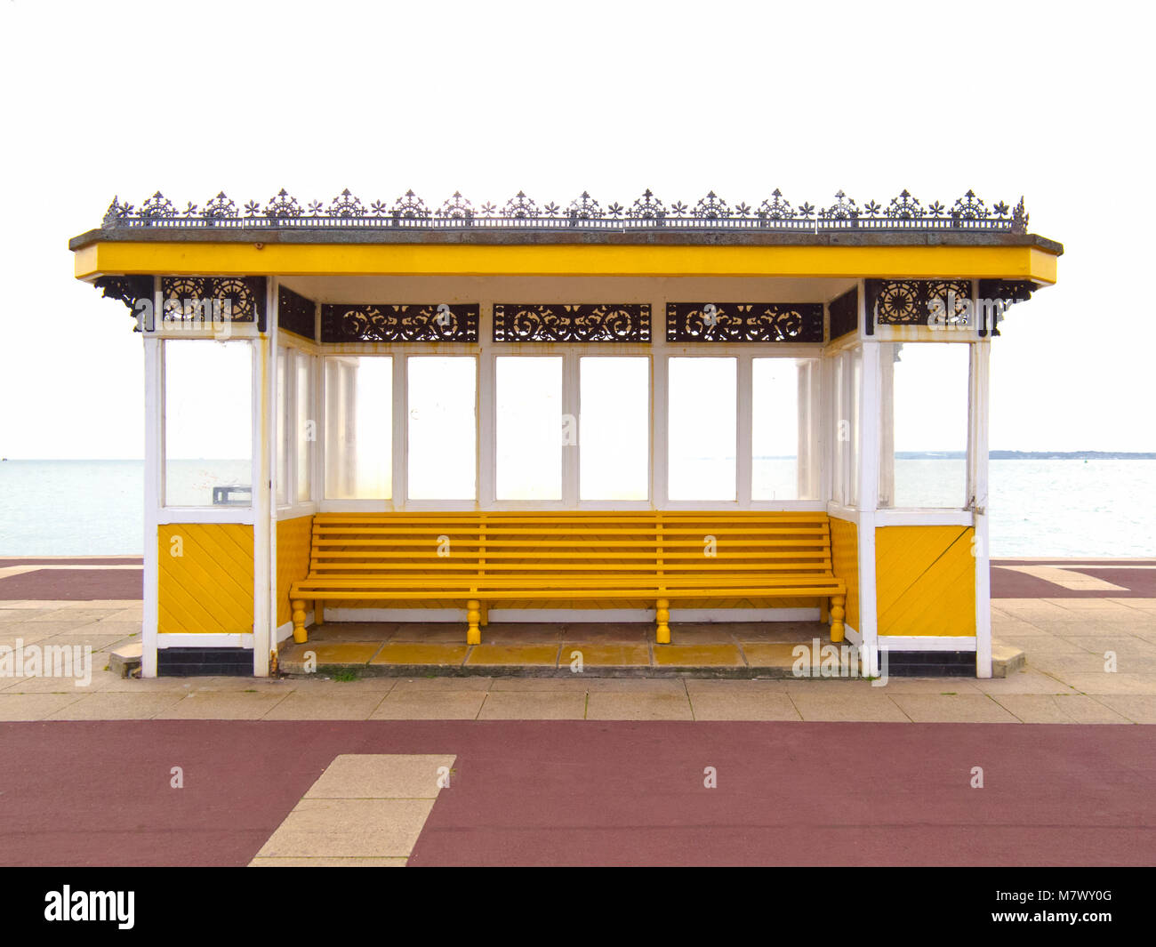 Victorian seaside town coastal wind shelter in yellow and white street furniture - Stock Image