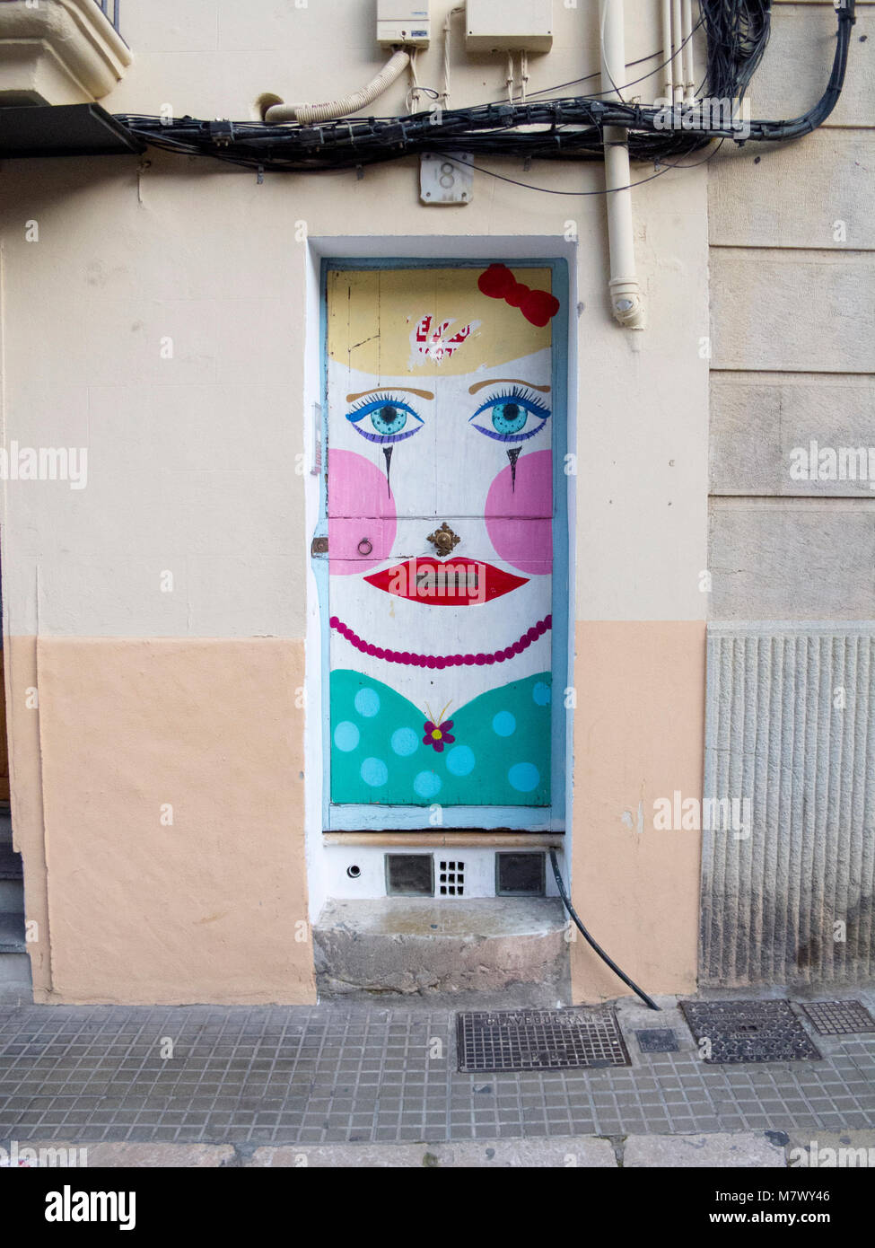 Artistic painted front door with face in old street - Stock Image