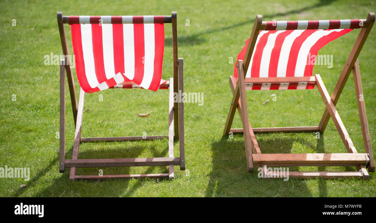 isolated unoccupied deck chairs in English garden - Stock Image