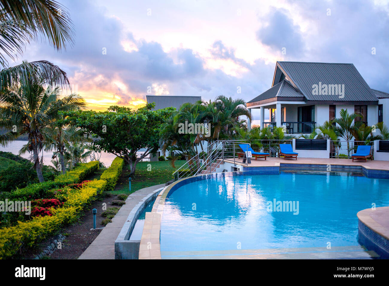 View of luxury villas with swimming pool and seats surrounded by palms on Fiji island during beautiful sunrise. - Stock Image