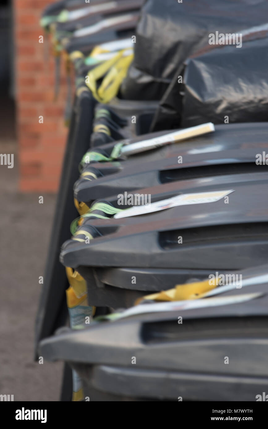 row of grey UK wheelie bins in a line with wall in background - Stock Image