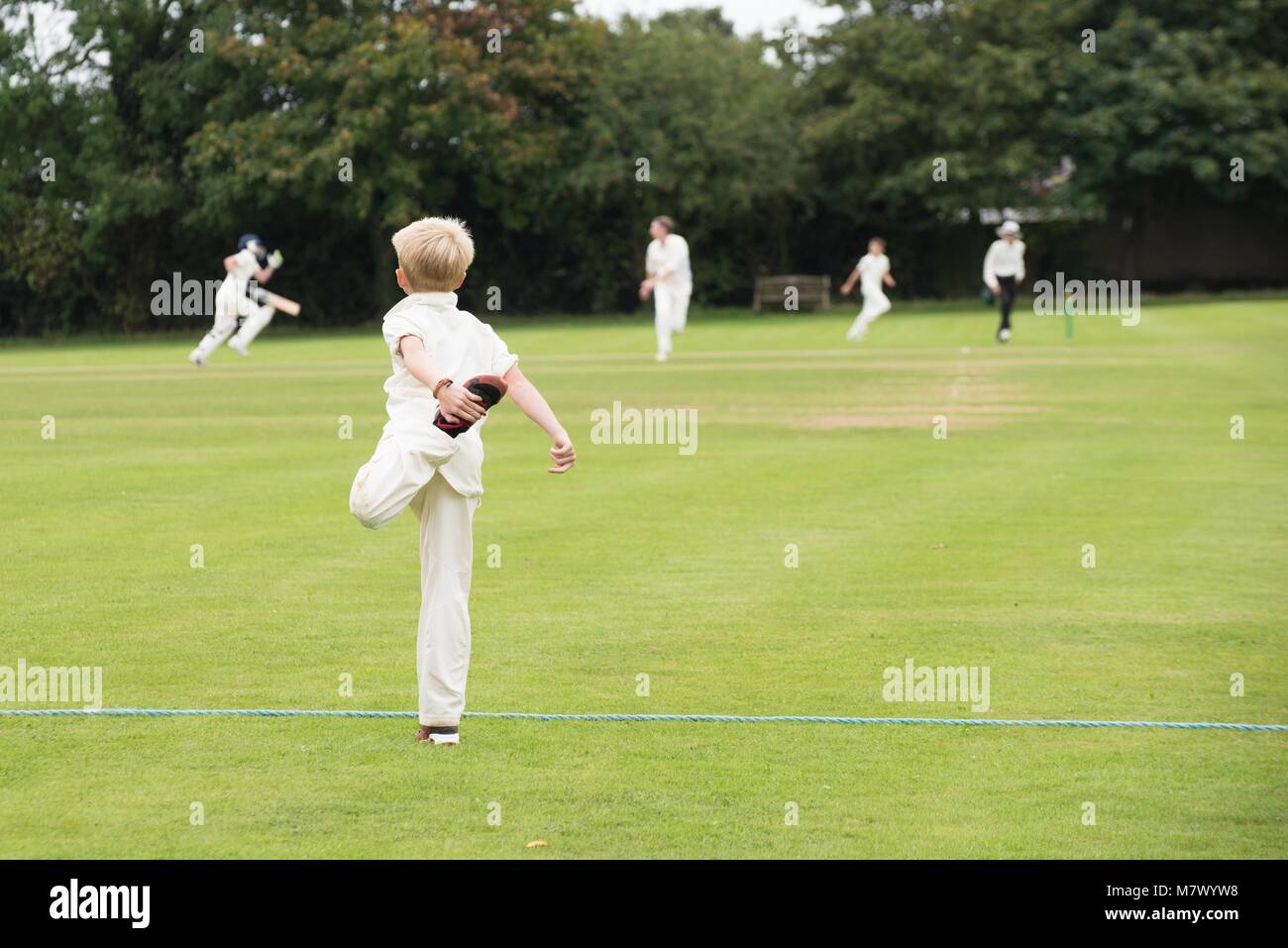 school youth player warming up for village cricket game in the UK in summer - Stock Image
