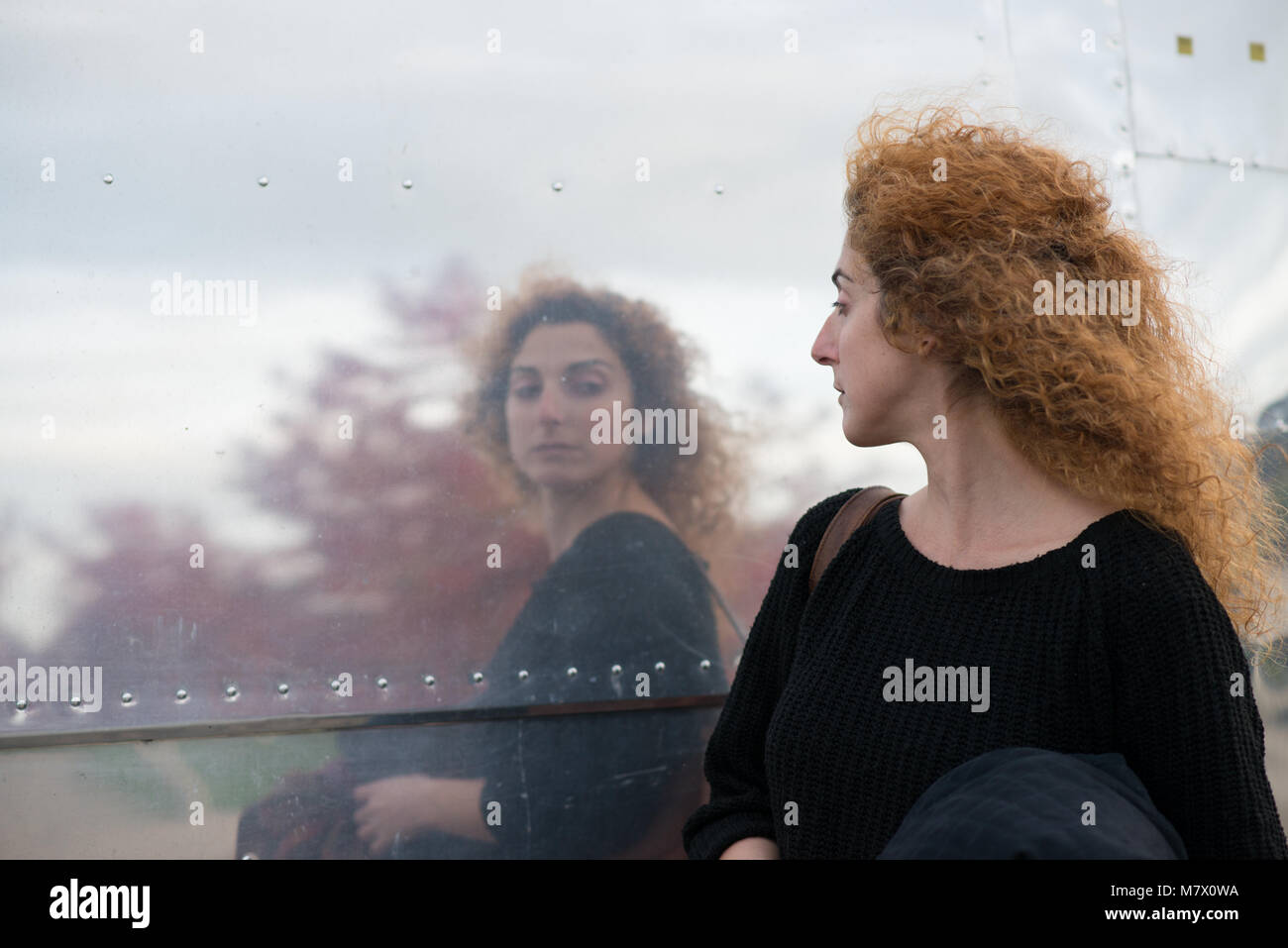 woman taking a passing look at reflection in side of American style diner like a huge mirror - Stock Image