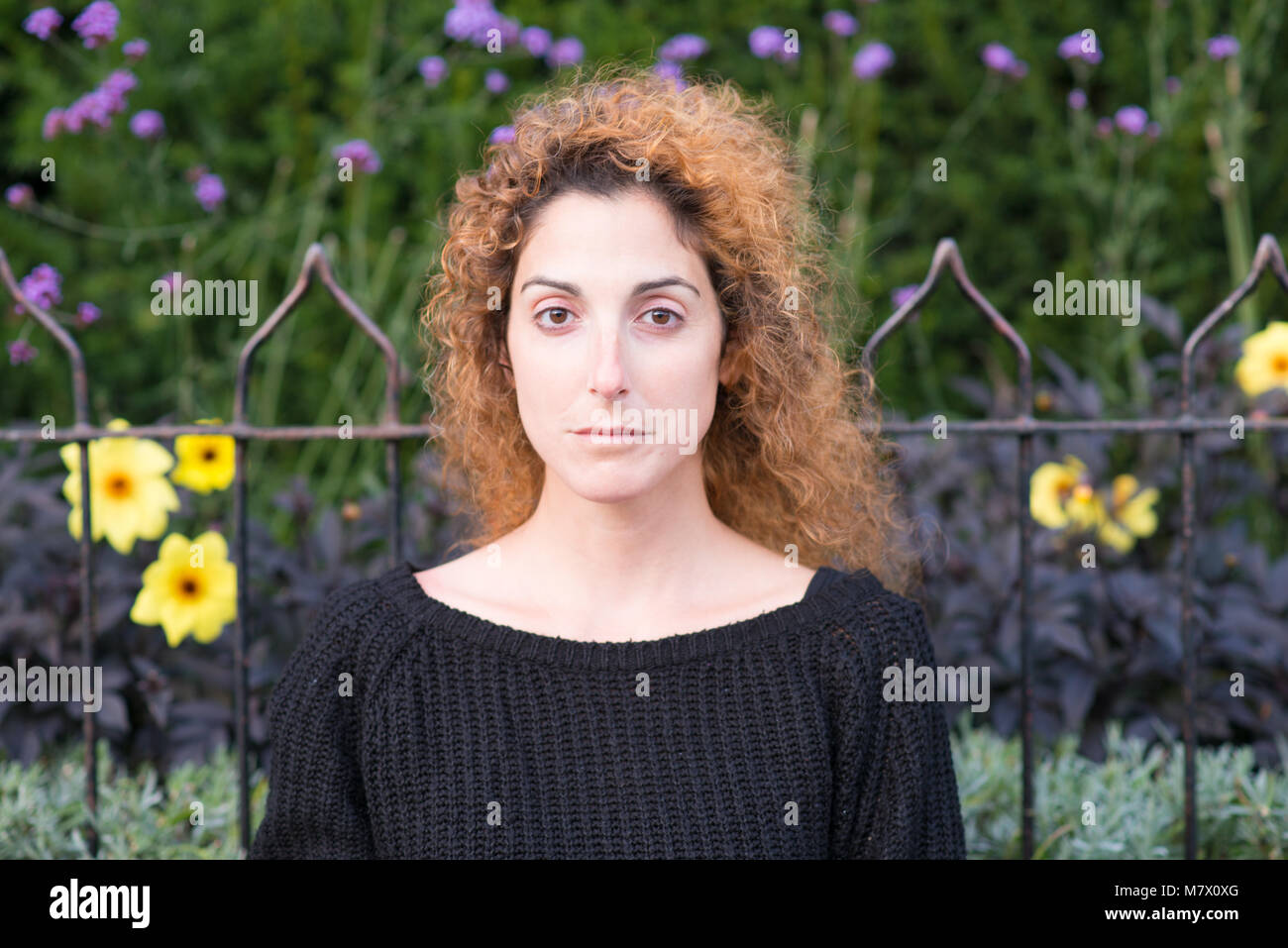 UK Stratford upon Avon 12th October 2017 woman with red curly hair blowing in front of  face and autumn fall flowers - Stock Image