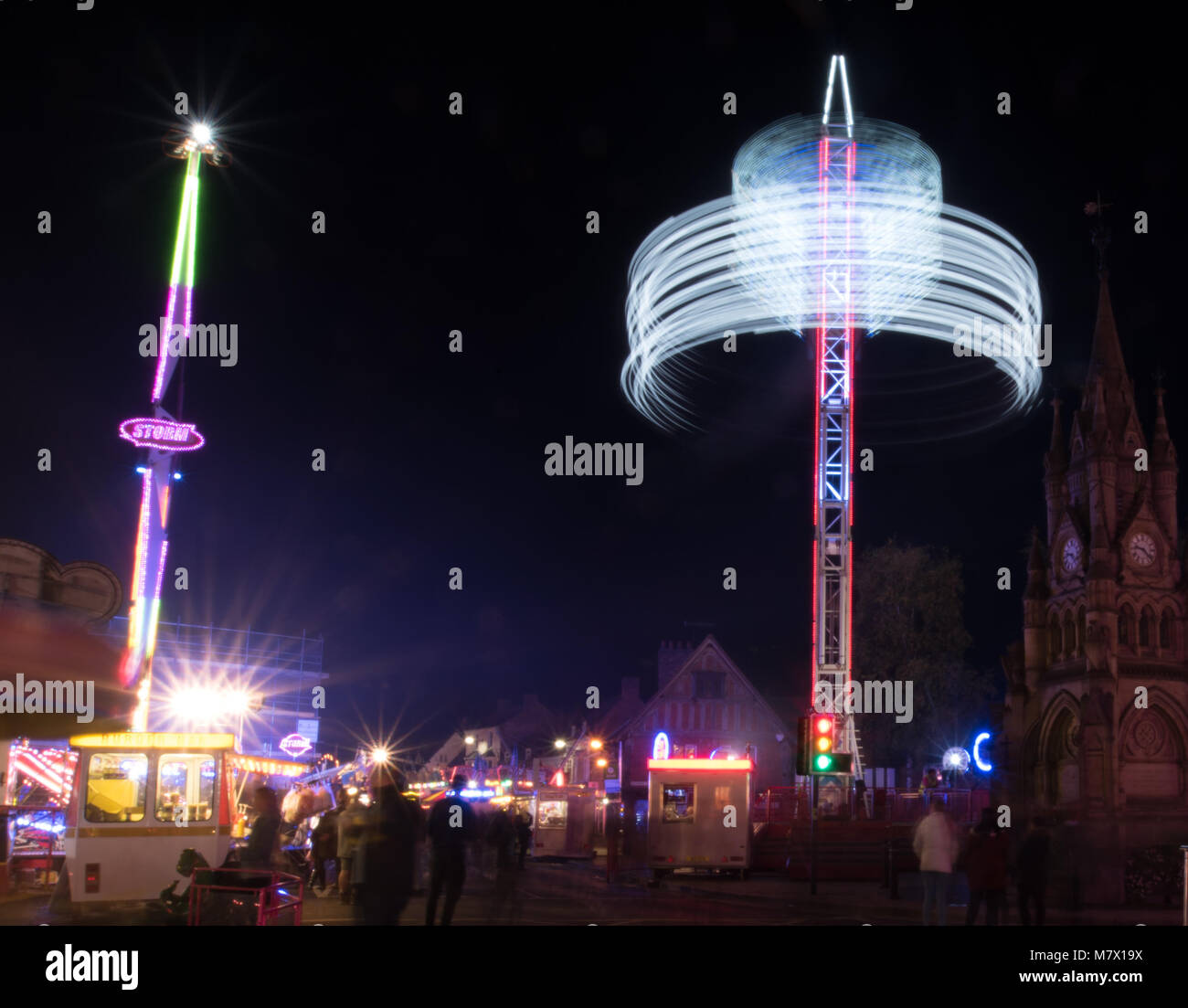 ghostly people at funfair in town centre with motion blur Stock Photo